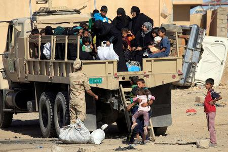 Displaced Iraqi people who fled from clashes ride in a military truck during a battle between Iraqi forces and Islamic state militants in western Mosul, Iraq, May 17, 2017. REUTERS/ Alaa Al-Marjani