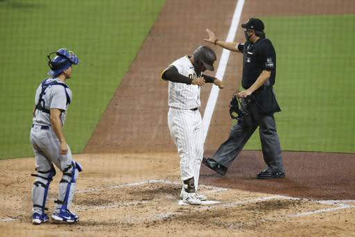 San Diego Padres' Trent Grisham, center, crosses home plate after hitting a solo home run off Los Angeles Dodgers starting pitcher Clayton Kershaw in the sixth inning of a baseball game Monday, Sept. 14, 2020, in San Diego. (AP Photo/Derrick Tuskan)