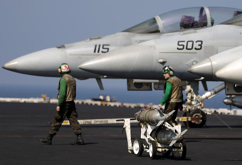 A bomb sits next to US Navy F-18 jet fighters on an aircraft carrier in the Gulf of Oman on January 30, 2014 (AFP Photo/Patrick Baz)
