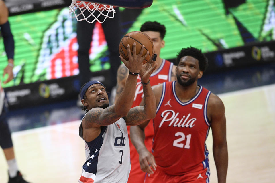 Washington Wizards guard Bradley Beal (3) goes to the basket past Philadelphia 76ers center Joel Embiid (21) during the first half of an NBA basketball game Friday, March 12, 2021, in Washington. (AP Photo/Nick Wass)