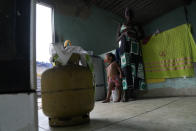 Lady Laurentino, 74, stands near an empty cooking gas cylinder at her home in Jardim Gramacho favela of Rio de Janeiro, Brazil, Monday, Oct. 4, 2021. Laurentino says she is cooking with wood because she doesn't have money to buy another gas cylinder. (AP Photo/Silvia Izquierdo)