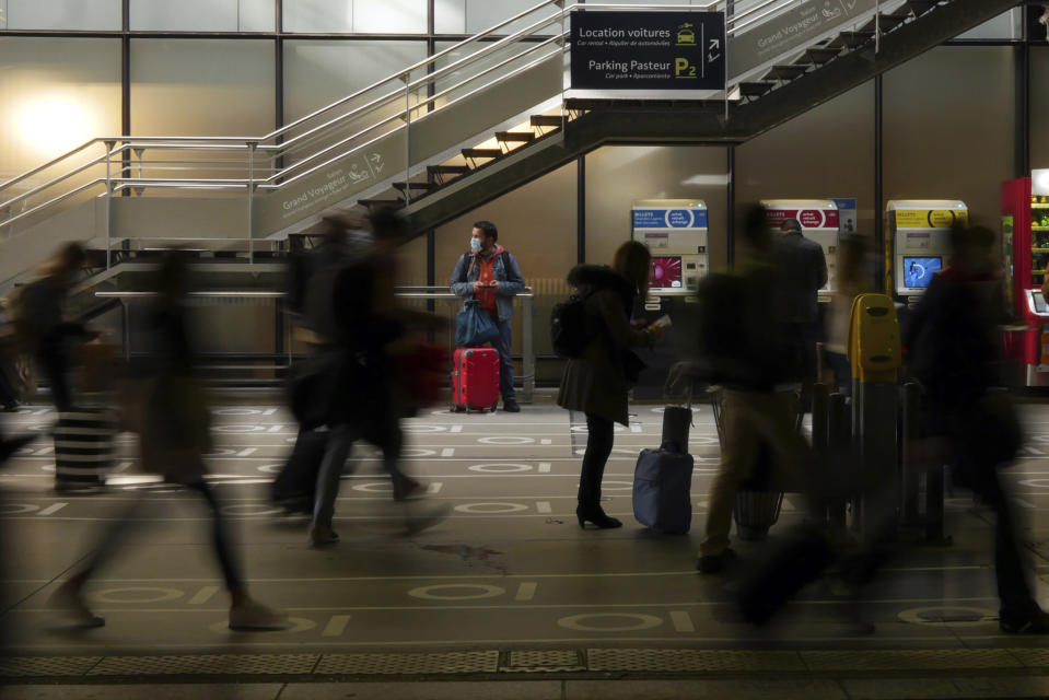 """A traveler waits to board a train at the Montparnasse railway station, in Paris, Friday, April 2, 2021. With France now Europe's latest virus danger zone, Macron on Wednesday ordered temporary school closures nationwide and new travel restrictions. But he resisted calls for a strict lockdown, instead sticking to his """"third way"""" strategy that seeks a route between freedom and confinement to keep both infections and a restless populace under control until mass vaccinations take over. (AP Photo/Thibault Camus)"""