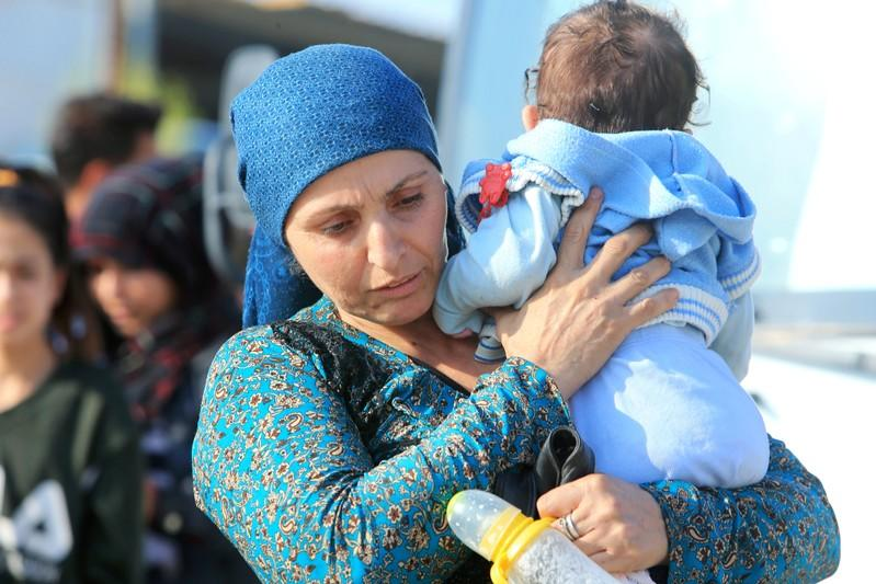 A displaced Syrian woman, who fled violence after the Turkish offensive in Syria, carries her baby upon arrival at a refugee camp in Bardarash on the outskirts of Dohuk