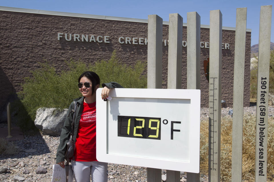 Jing Jing, a student from China, poses in front of a temperature gauge at Death Valley National Park in California on June 29. (Steve Marcus/Reuters)