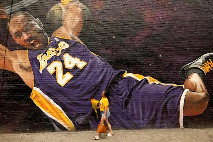 """LOS ANGELES, CA - AUGUST 23, 2020 - - Elizabeth Munoz, from Huntington Park, brings flowers to leave at a Kobe Bryant mural on what would have been his 42nd birthday along Hill Street in downtown Los Angeles on August 23, 2020. Munoz, her sister and nephew, were visiting as many murals of the late Lakers star and leaving flowers to wish him a Happy Birthday. """"Thanks for all the memories. We'll never forget you,"""" Munoz said. The mural was created by L.A. native artist Enkone. (Genaro Molina / Los Angeles Times)"""