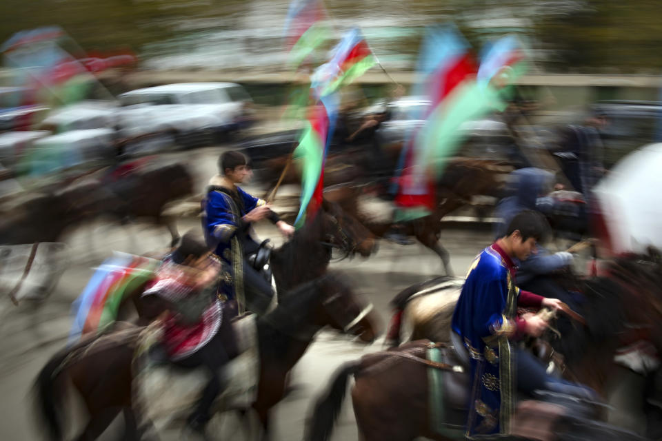 Azerbaijani with national flags ride horses as they celebrate the transfer of the Lachin region to Azerbaijan's control, as part of a peace deal that required Armenian forces to cede the Azerbaijani territories they held outside Nagorno-Karabakh, in Aghjabadi, Azerbaijan, Tuesday, Dec. 1, 2020. Azerbaijan has completed the return of territory ceded by Armenia under a Russia-brokered peace deal that ended six weeks of fierce fighting over Nagorno-Karabakh. Azerbaijani President Ilham Aliyev hailed the restoration of control over the Lachin region and other territories as a historic achievement. (AP Photo/Emrah Gurel