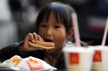 A child eats a hamburger outside a McDonald's fast food restaurant in downtown Milan