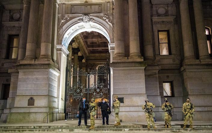 "The National Guard defends City Hall in response to a ""Stop the Steal"" protest by Trump supporters, Philadelphia, Pennsylvania - Shutterstock"