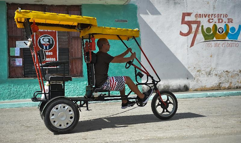 """A man rides a bike taxi past a wall reading """"57th anniversary, CDR. The neighborhood unites us"""" (AFP Photo/Yamil LAGE)"""