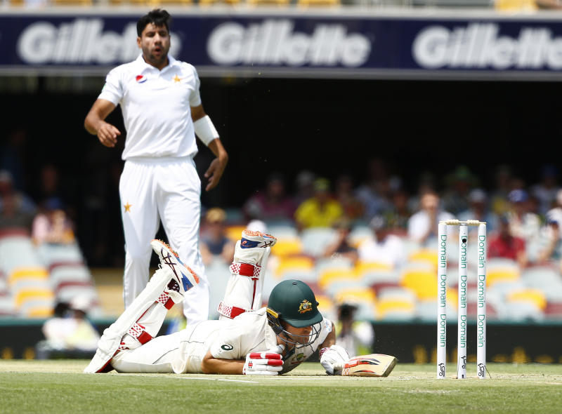 Australia's Joe Burns, front, falls after slipping in his crease as Pakistan's Imran Khan, back, watches on during their cricket test match in Brisbane, Australia, Friday, Nov. 22, 2019. (AP Photo/Tertius Pickard)