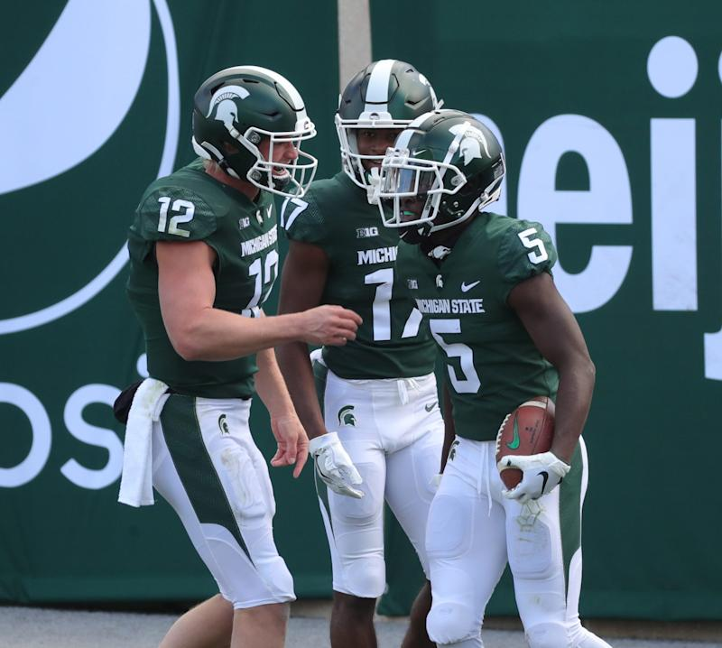 (From left) Michigan State quarterback Rocky Lombardi and wide receiver Tre Mosley congratulate wide receiver Jayden Reed after his touchdown during MSU's 38-27 loss on Saturday, Oct. 24, 2020, at Spartan Stadium.