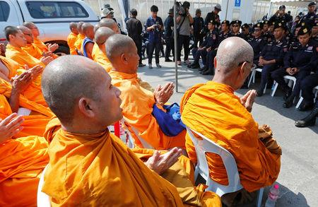 Buddhist monks chant inside Dhammakaya temple while police block access to the place in Pathum Thani province