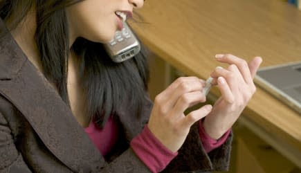Woman on cellular phone while filing her nails