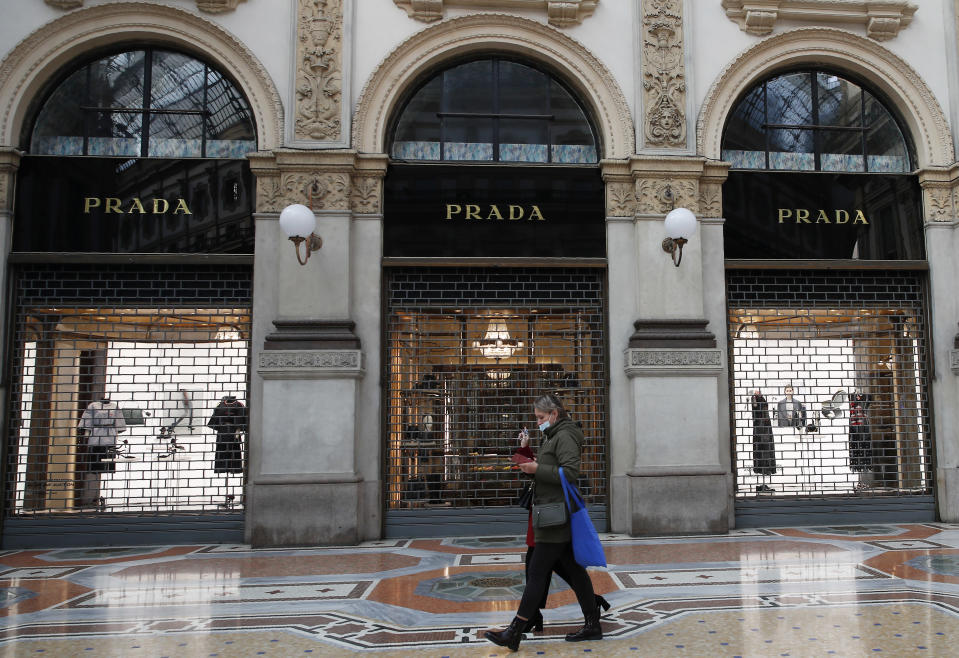 Women walk in the Vittorio Emanuele II gallery shopping arcade in Milan, Italy, Friday, Nov. 6, 2020. Lombardy is among the four Italian regions classified as red zones, where a strict lockdown was imposed starting Friday - to be reassessed in two weeks - in an effort to curb the COVID-19 infections growing curve. Starting today, only shops selling food and other essentials are allowed to open. (AP Photo/Antonio Calanni)