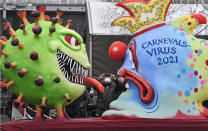A political carnival float depicting the coronavirus vs the carnival virus is rolled out to be shown in the streets when the traditional carnival parade was canceled due to the coronavirus pandemic in Duesseldorf, Germany, Monday, Feb. 15, 2021. Eight floats are pulled through the empty streets in Duesseldorf, where normally hundreds of thousands of people would celebrate the street carnival. (AP Photo/Martin Meissner)