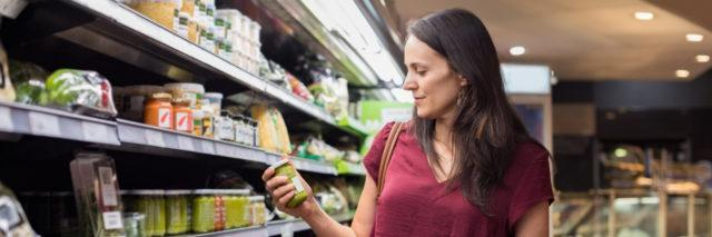 woman shopping at the grocery store and holding up a jar of something to read