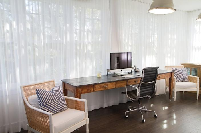 This weathered wooden desk fits perfectly with the other breezy pieces in this Hamptons-style office
