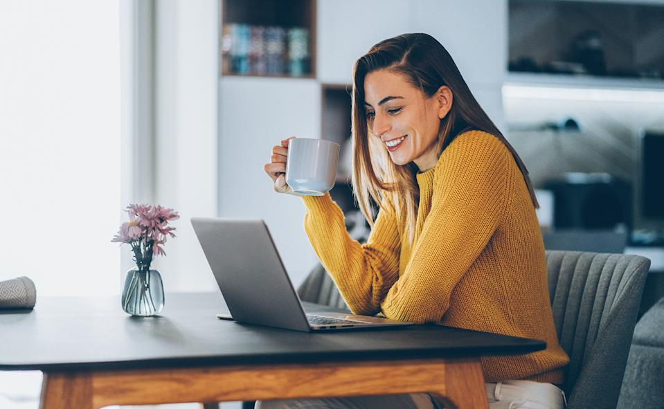 Young woman working at home, typing on laptop. (Getty Images)