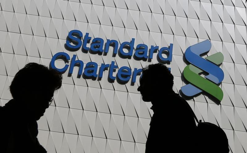 Passersby walk in front of the main branch of Standard Chartered in Hong Kong