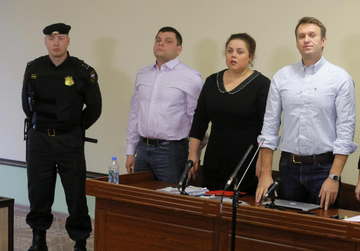 A bum bailiff guards as Russian opposition leader Alexei Navalny, right, his former colleague Pyotr Ofitserov, second left, and lawyer Svetlana Davydova, second right, stand in a court room in Kirov, Russia, Wednesday, Oct. 16, 2013. A Russian courthouse in Kirov set Navalny free in July, the day after he was convicted of embezzlement and sentenced to five years in prison. Navalny has appealed both the conviction and the sentence. (AP Photo/Dmitry Lovetsky)