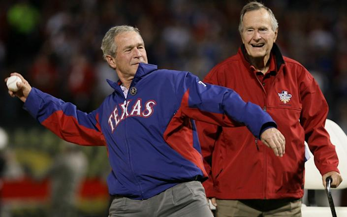 George W Bush throws out the first pitch in front of his father, George H W Bush, at the fouth game of the 2010 MLB World Series - Getty Images
