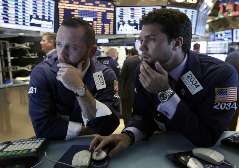 Specialists Christopher Gildea, left, and Joseph Dreyer, confer at their posts on the floor of the New York Stock Exchange Monday, July 22, 2013. The stock market edged higher as a big week of earnings kicked off Monday, with mixed results from a handful of large U.S. companies. (AP Photo/Richard Drew)
