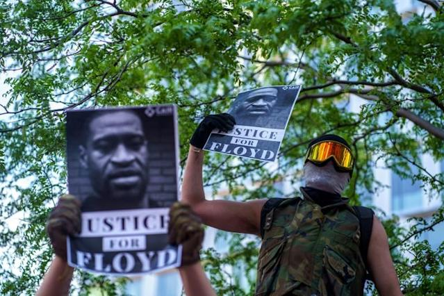 A masked protester in the US city of Minneapolis holds a sign demanding justice for George Floyd, the African-American man who died in police custody on May 25, 2020, sparking fiery riots and accusations of police racism (AFP Photo/kerem yucel)