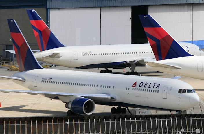 FILE - In this April 20, 2010 file photo, Delta Air Lines jets are parked at John F. Kennedy International Airport, in New York. U.S. Customs and Border Protection will issue a new policy directive under a settlement agreement that states airline passengers are not required to consent to document checks. The settlement comes in a lawsuit filed by passengers aboard a Delta flight from San Francisco to New York's Kennedy Airport in February 2017 who were met by CBP officers and forced to hand over identification as they deplaned. It was just a few weeks after President Donald Trump's first travel ban. (AP Photo/Mark Lennihan)