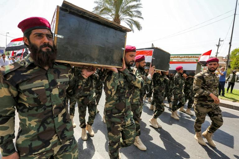 Members of Iraq's Hashed al-Shaabi paramilitary forces march in a symbolic funeral parade in the capital Baghdad, in remembrance of those killed in a US raid against one of the Hashed's brigades