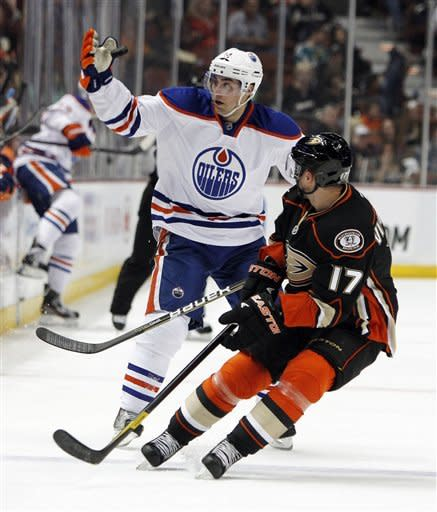 Edmonton Oilers right wing Jordan Eberle, left, reaches up for an airborne puck as he battles Anaheim Ducks defenseman Lubomir Visnovsky (17) in the first period of an NHL hockey game in Anaheim, Calif., Sunday, April 1, 2012. (AP Photo/Christine Cotter)