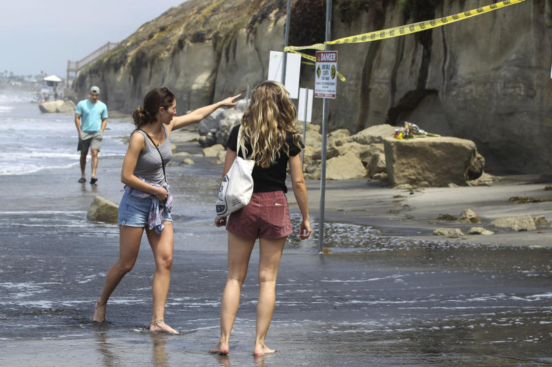 People look at the sand rock debris left from Friday's sea cliff collapse, which killed three people, near the Grandview Beach access stairway in the beach community of Leucadia, on Saturday, Aug. 3, 2019 in Encinitas, Calif. Officials have reopened much of the Southern California beach where the sea cliff collapsed.  (Hayne Palmour IV/The San Diego Union-Tribune via AP)