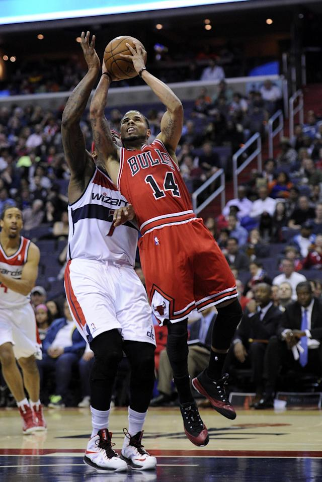 Chicago Bulls guard D.J. Augustin (14) goes to the basket against Washington Wizards forward Al Harrington (7) during the first half of an NBA basketball game, Saturday, April 5, 2014, in Washington. Harrington was called for a foul on the play. (AP Photo/Nick Wass)