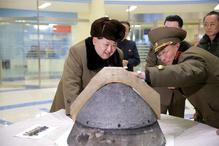 FILE PHOTO: KCNA file picture shows North Korean leader Kim Jong Un looking at a rocket warhead tip after a simulated test of atmospheric re-entry of a ballistic missile