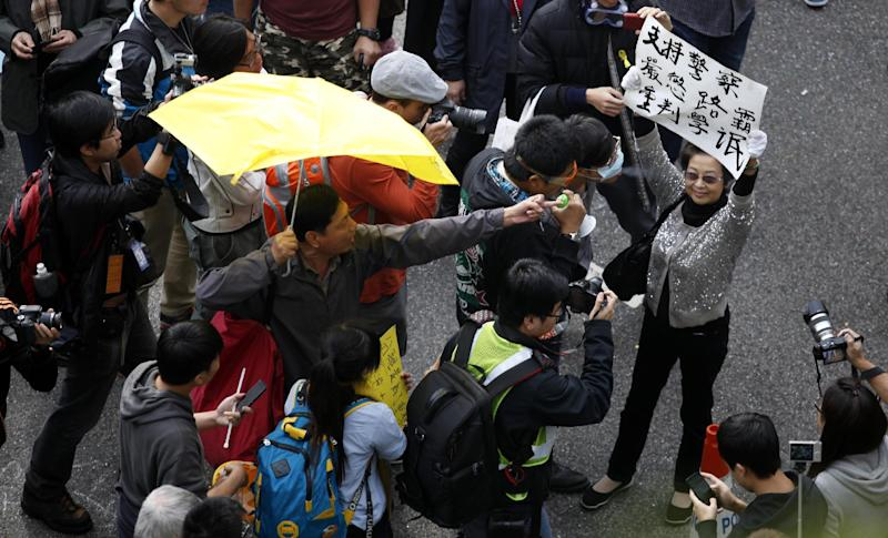 Pro-democracy protesters (left) shout at a pro-government demonstrator holding up a placard in Hong Kong on December 11, 2014 (AFP Photo/Isaac Lawrence)