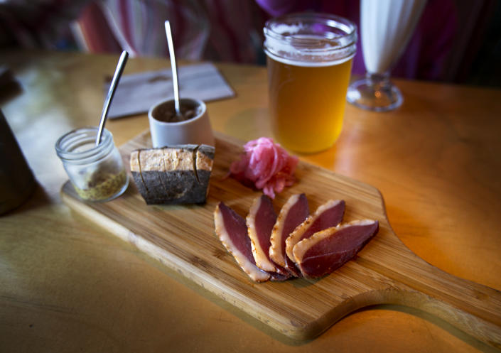 This photo made Friday, July 12, 2013, shows a charcuterie board served with duck, warm baguette and handcrafted condiments, at Duckfat, a small sandwich shop in Portland, Maine. (AP Photo/Robert F. Bukaty)