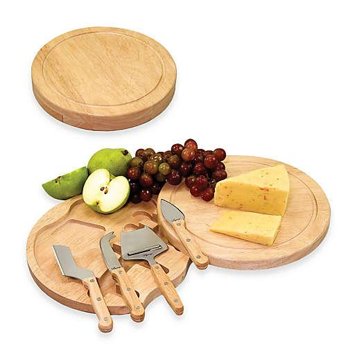 Round wooden cheese board and slicing tools topped with grapes and cheese