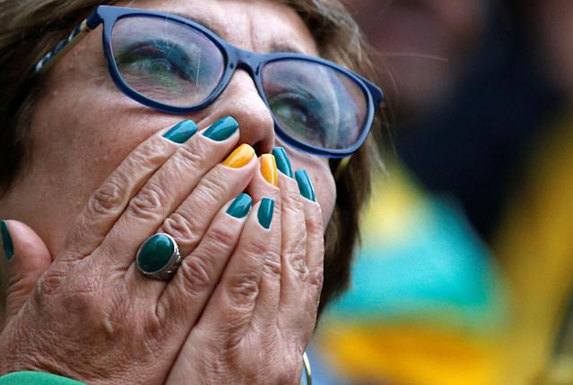 A fan reacts as she watches the broadcast of the FIFA World Cup Group E soccer match between Brazil and Switzerland, in Sao Paulo, Brazil June 17, 2018. REUTERS/Leonardo Benassatto
