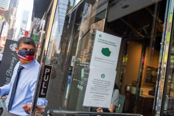 PHOTO: A man with a mask walks out of a Starbucks where a 'if you are fully vaccinated, facial coverings are optional' sign is displayed on the door in New York, May 26, 2021. (Alexi Rosenfeld/Getty Images, FILE)