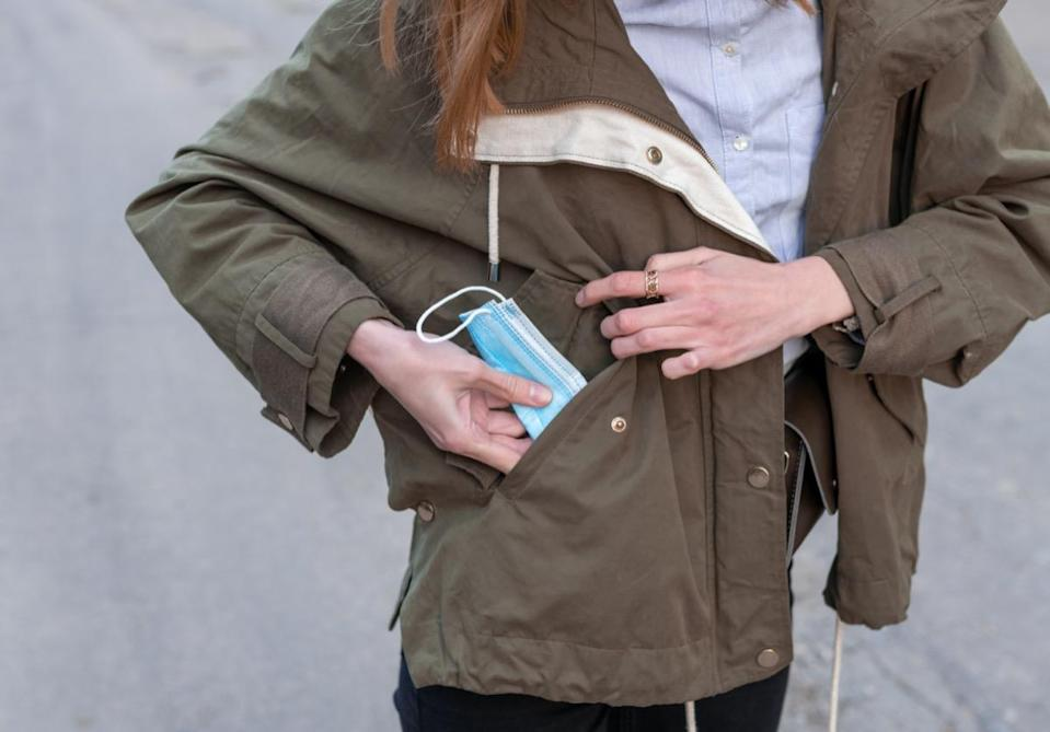 girl's hands pulling surgical protective face mask out of her green pocket,
