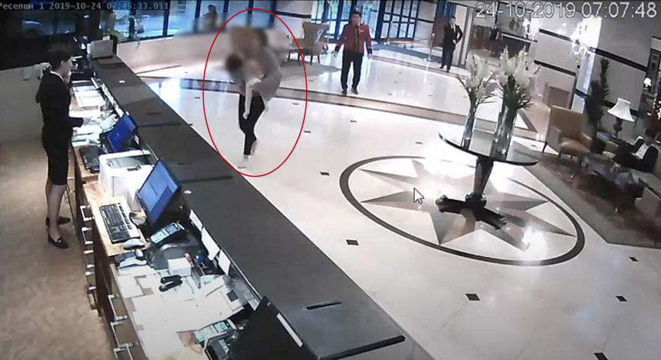 Madina carrying an unconscious Sophia as she runs up to the hotel's front desk. Source: East2West/Australscope