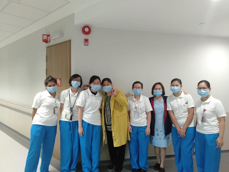 Ms Jiang (in yellow outfit) posing with doctors and nurses at the National Centre for Infectious Diseases. (PHOTO: Jiang via MOH)