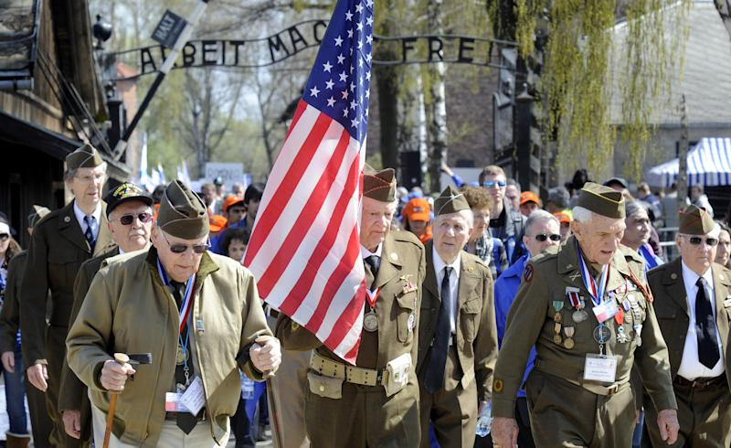 A group of U.S. Army veterans who took part in liberating Nazi death camps walk through the entrance gate of the former Nazi Death Camp Auschwitz-Birkenau, in Oswiecim, southern Poland, Thursday, April 19, 2012, as they take part in the annual March of the Living to commemorate Holocaust victims. Walking with the flag is Frederick Carrier, one of the U.S. soldiers who helped liberate Buchenwald. (AP Photo/Alik Keplicz)