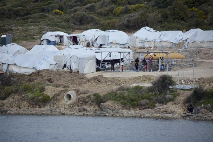 FILE - In this file photo dated Monday, March 29, 2021, migrants gather outside their tents a refugee camp, on the eastern Aegean island of Lesbos, Greece. Greek authorities on island of Lesbos said Tuesday July 20, 2021, they are drawing up a criminal case, including on charges of espionage, against 10 people, all foreign nationals, for allegedly helping migrants enter the country illegally. No suspects have been publicly identified. (AP Photo/Panagiotis Balaskas, FILE)