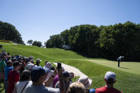 Dustin Johnson putts on the 11th green as spectators watch during the first round of the Travelers Championship golf tournament at TPC River Highlands, Thursday, June 24, 2021, in Cromwell, Conn. (AP Photo/John Minchillo)