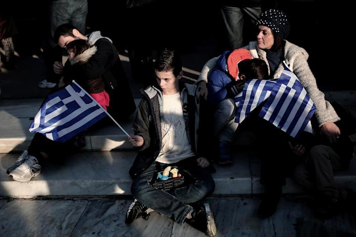 A boy holds a Greek flag during an anti-austerity, pro-government demonstration in front of the Parliament in Athens, on February 15, 2015 (AFP Photo/Angelos Tzortzinis)