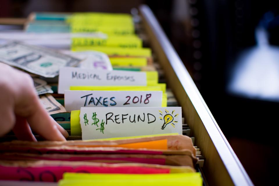 Tax refund conceptual tax season tax preparation photography with files and tax forms in filing cabinet and words refund and taxes 2018 written on file folders  with light bulb for ideas and US dollar cash in background