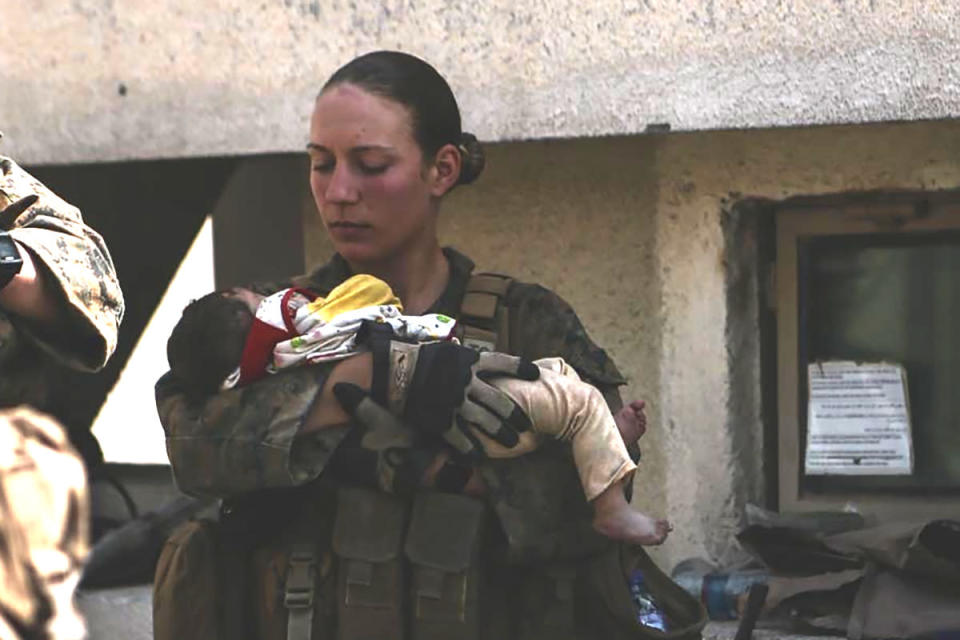 This undated photo provided by U.S. Department of Defense twitter page posted Aug. 20, 2021 shows Sgt. Nicole Gee holding a baby at Hamid Karzai International Airport in Kabul, Afghanistan. Officials said Saturday, Aug. 28, 2021, that Sgt. Nicole Gee of Sacramento, Calif., was killed in Thursday's bombing in Kabul, Afghanistan. (U.S. Department of Defense via AP)