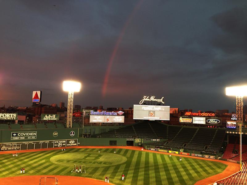 Boston Red Sox players take batting practice as a rainbow appears in the sky above Fenway Park Tuesday, Oct. 22, 2013, in Boston. The Red Sox are scheduled to host the St. Louis Cardinals in Game 1 of baseball's World Series on Wednesday. (AP Photo/Ron Blum)