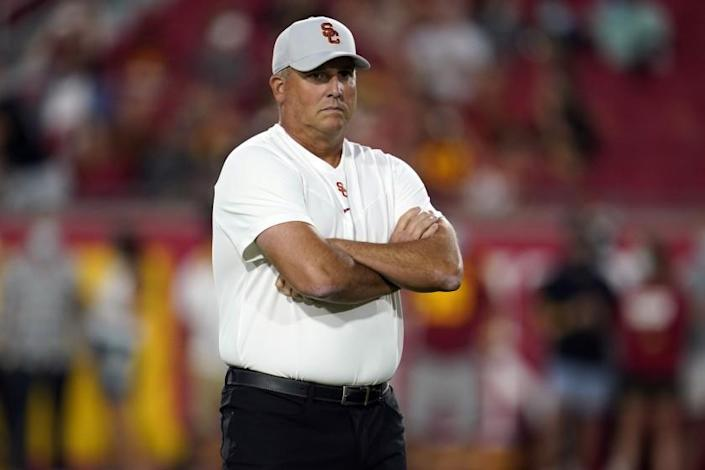 Clay Helton stands with arms crossed as he watches the Trojans warm up before the Stanford game.