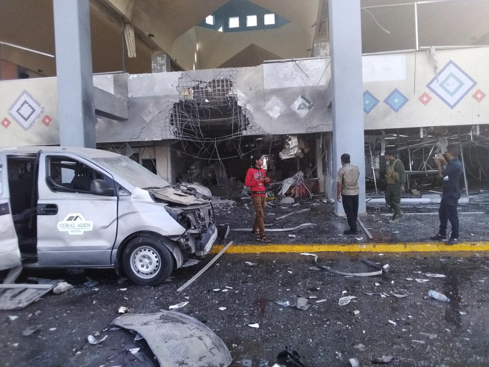Bystanders and a soldier stand near a damaged portion of the airport of Yemen's southern city of Aden's after an explosion, Wednesday, Dec. 30, 2020. The blast struck the airport building shortly after a plane carrying the newly formed Cabinet landed on Wednesday. No one on the government plane was hurt. (AP Photo/Majid Saleh)
